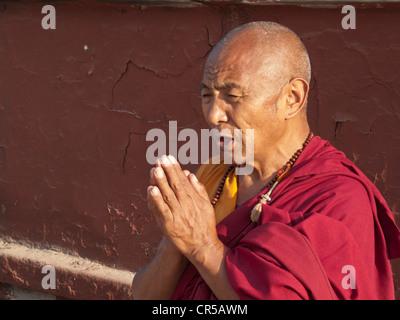 Buddhist monk praying in front of Boudnath stupa, Boudnath, Kathmandu, Nepal, South Asia - Stock Photo