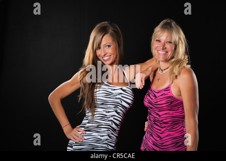 Two attractive women - Adult mother and daughter in fitness outfits - Stock Photo