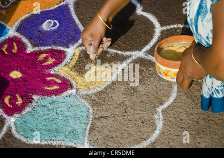 Woman making Rangoli, decorative sand designs in the streets of Madurai during a Hindu festival, meant as sacred - Stock Photo