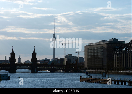 View of the river Spree with the bridge Oberbaumbruecke and the televisiontower in the background during a summer - Stock Photo