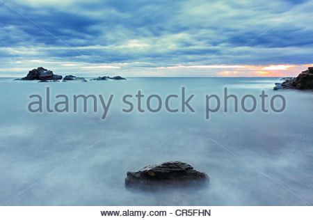 dawn in cabo de palos, murcia, spain,silk effect in the water, red and orange reflection in the grey water. Spanish - Stock Photo