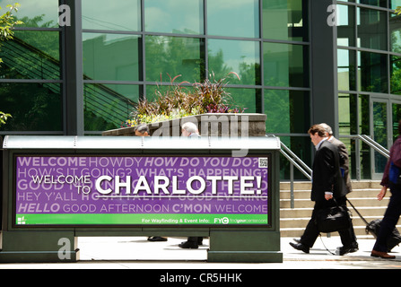 Pedestrians outside the Charlotte Convention Center walk past a sign that reads 'Welcome to Charlotte!' - Stock Photo