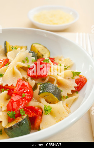 A bowl of pasta bows or farfalle with roast courgettes or zucchini, red pepper and tomato with olive oil and herbs. - Stock Photo