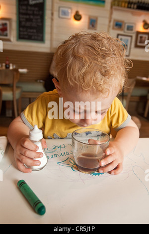 Three year old boy waiting for his food in fish and chip shop, Dartmouth Devon, England, United Kingdom. - Stock Photo
