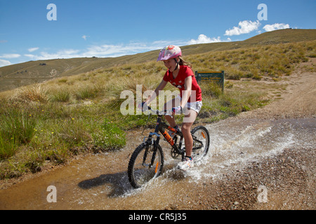 Young mountain biker riding through water race, Carrick Track, Carrick Range, Central Otago, South Island, New Zealand - Stock Photo