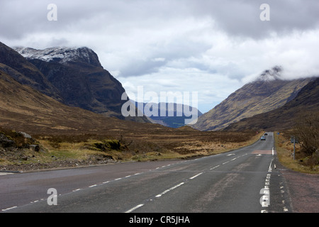road coming from rannoch moor leading to fort william via glencoe in the highlands of scotland with snow capped - Stock Photo