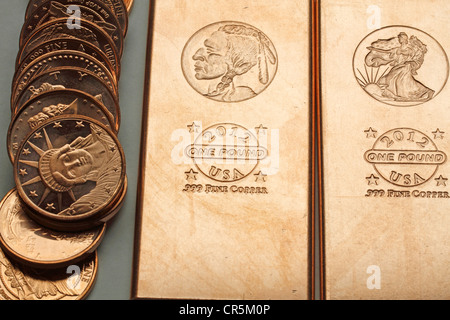 1 oz Copper coins and 1 pound copper bars - base metals popular with preppers to be used as currency in a cashless - Stock Photo