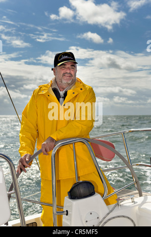 Skipper standing at the helm of his yacht - Stock Photo
