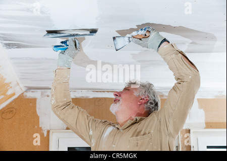 Craftsman plastering a ceiling - Stock Photo