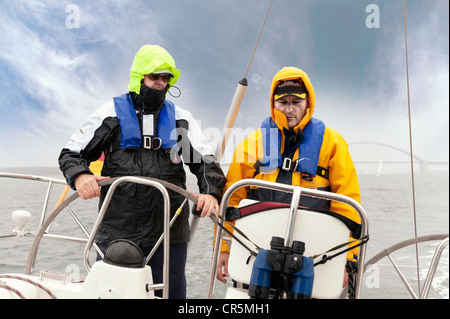 Two men standing on the stern of a yacht - Stock Photo