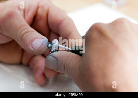 Hands of a dental technician with a grinder and metal crowns - Stock Photo