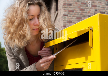 Young woman putting letter into a postbox - Stock Photo