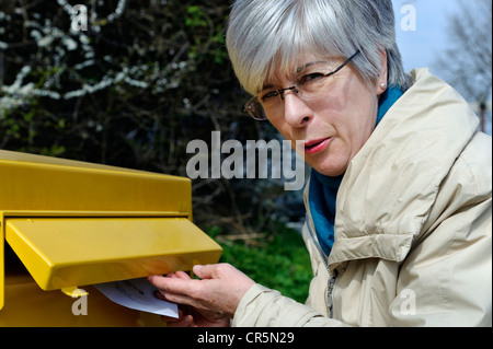 Woman putting a letter into a mailbox, Germany, Europe - Stock Photo
