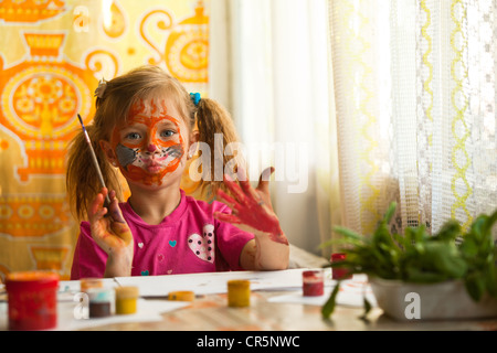 Beautiful little girl artist with paint of face. - Stock Photo