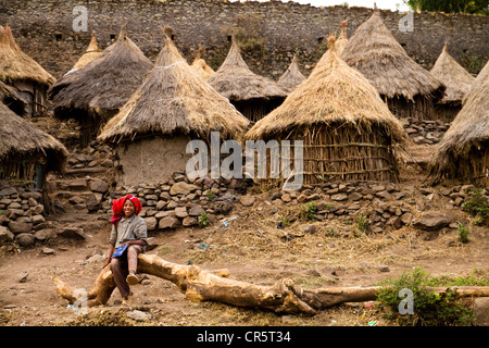 Boy in front of huts of a religious student's village near Debre Berhan Selassie Church, Gonder, Ethiopia, Africa - Stock Photo