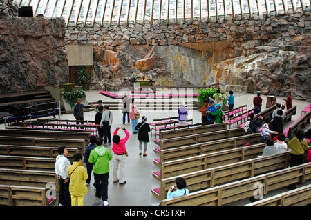 Asian tourists in the sanctuary of the Temppeliaukio Church in Helsinki, Finland, Europe - Stock Photo