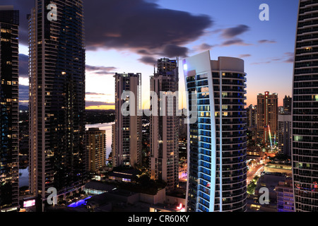 Residential towers stand in the night showing lights of the city skyline of the architectural designed Residential - Stock Photo