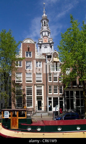 Traditional canal houses and church tower in the centre of Amsterdam - Stock Photo