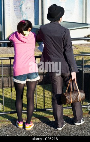Japan, Honshu Island, Tokyo, East Gardens of the Imperial Palace, trendy couple with a Louis Vuitton bag - Stock Photo