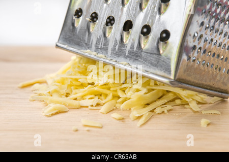 Grated cheese with grater on wooden chopping board against white background - Stock Photo