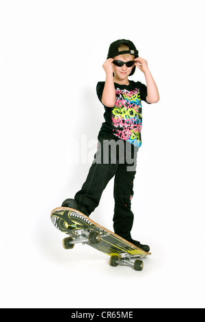 Studio image of Caucasian 8 year old boy with skateboard on a white background - Stock Photo