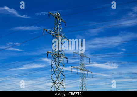 Two electricity pylons against blue sky with cirrostratus clouds - Stock Photo