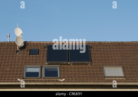 Roof with roof windows, satellite dishes and solar thermal panels, investment in property, PublicGround - Stock Photo