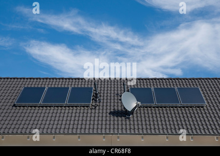 Solar panels to heat water, absorption areas on a roof of an apartment building, PublicGround - Stock Photo