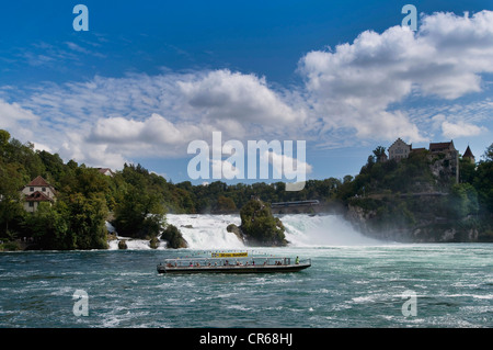 Rhine Falls near Schaffhausen, excursion boat with tourists cruising in front of it, Switzerland, Europe - Stock Photo
