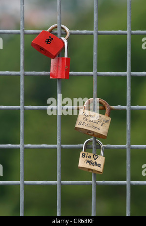 Padlocks on a wire grid, tokens of love - Stock Photo