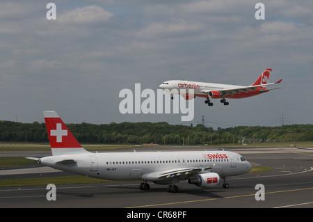 Passenger airplane of Swiss International Air Lines Ltd. on the runway, behind an airberlin airplane departing, - Stock Photo