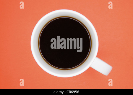 Cup of coffee on orange background, close up - Stock Photo