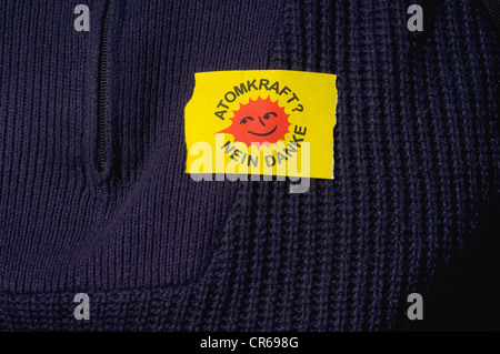 Yellow sticker 'Atomkraft nein danke', German for 'nuclear power, no thanks', on a blue knitted sweater - Stock Photo