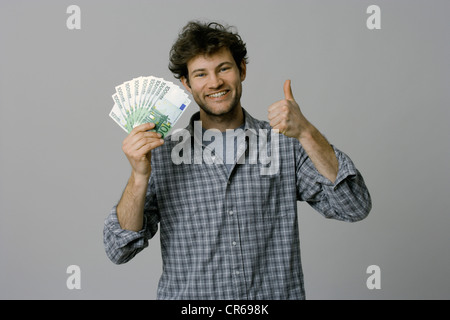 Young man holding 100 Euro bills and showing thumbs up - Stock Photo