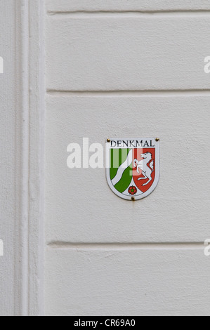 Plaque of a listed building in North Rhine-Westphalia on a white house wall - Stock Photo