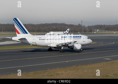 Air France Airbus A319-111 passenger jet on the runway of Duesseldorf International Airport, behind, a SAS Jet taking - Stock Photo