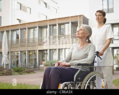 Germany, Cologne, Caretaker pushing senior women in wheelchair - Stock Photo