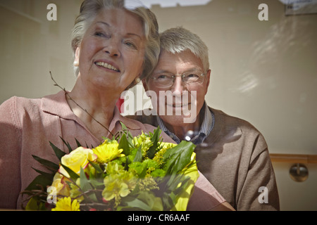 Germany, Cologne, Senior couple with flower bouquet, smiling - Stock Photo