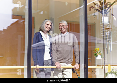 Germany, Cologne, Senior couple looking through window, smiling - Stock Photo