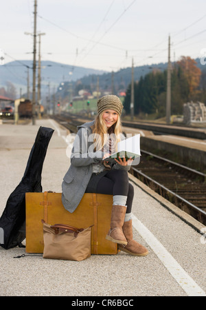 Austria, Teenage girl with suitcase on train station - Stock Photo