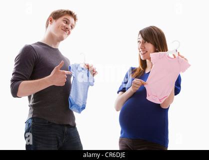 Studio Shot of young couple holding onesie - Stock Photo
