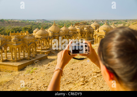 India, Rajasthan,Jaisalmer, Female tourist photographing at Bada Bagh Cenotaphs - Stock Photo