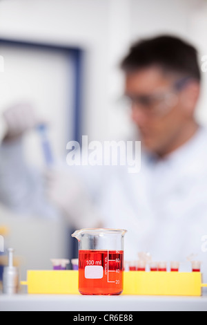 Germany, Bavaria, Munich, Red liquid in beaker, scientist doing medical research in background - Stock Photo