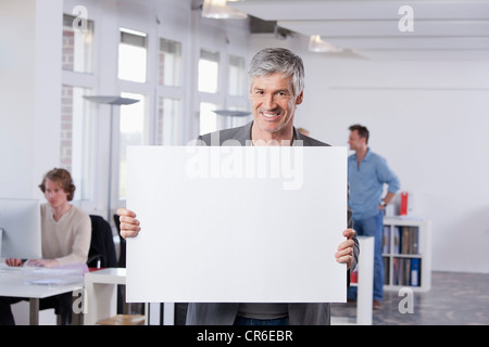 Germany, Bavaria, Munich, Mature man holding placard in office - Stock Photo