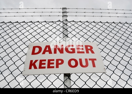 Danger Keep Out sign on a chain link fence topped with barbed wire. - Stock Photo