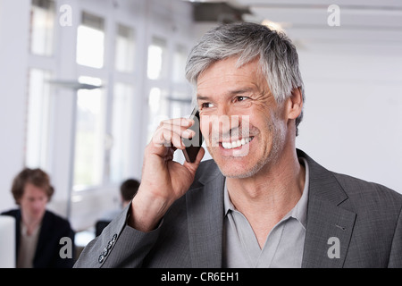Germany, Bavaria, Munich, Mature man on mobile phone, colleagues working in background - Stock Photo