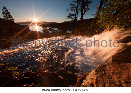 The sunrise lights up Eagle Falls which flows high above Emerald Bay and Lake Tahoe on the border of California - Stock Photo