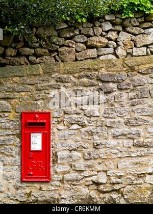 Royal Mail GR post box set into a stone wall in the village of Matlock Bath Derbyshire Peak District England UK - Stock Photo