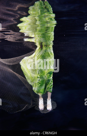 Mixed race woman in dress swimming under water