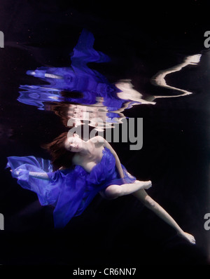Caucasian woman in dress swimming under water - Stock Photo